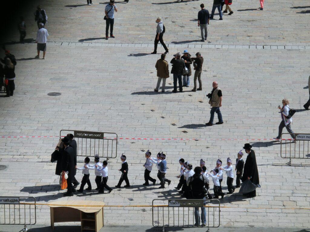 ユダヤ教超正統派の一家。子どもたちが列車ごっこをして歩いています。