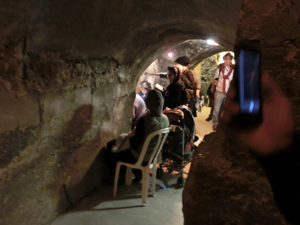 当時の城壁の前で旧約聖書を読むユダヤ教徒。